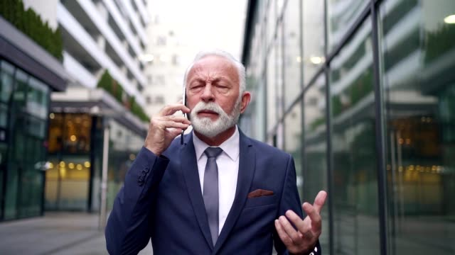 senior businessman displeased with news he got on cellphone - displeased stock videos & royalty-free footage
