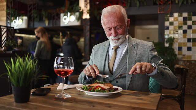 vidéos et rushes de homme d'affaires aîné appréciant dans un déjeuner de restaurant - restaurant