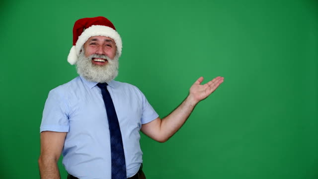 senior businessman in hat of santa claus shows copy space and shows the thumb on a green background - shirt and tie stock videos & royalty-free footage