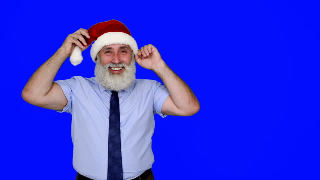 senior businessman in hat of santa claus shows copy space and shows the thumb on a blue background - santa hat stock videos and b-roll footage