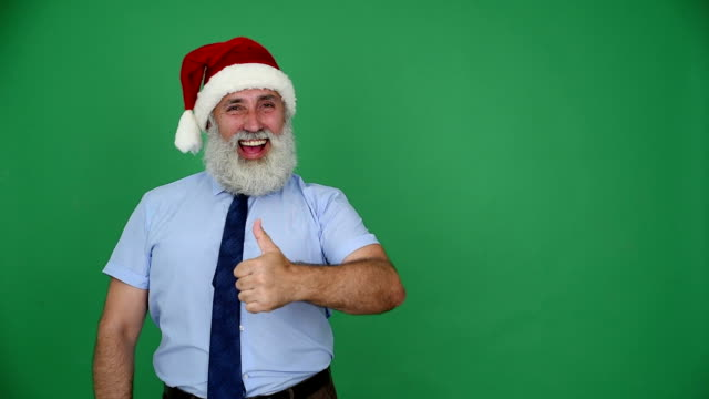 senior businessman in hat of santa claus shows up space and shows the thumb on a green background - shirt and tie stock videos & royalty-free footage