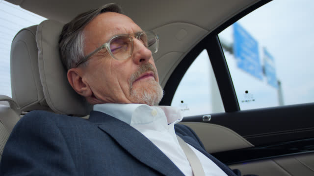 senior businessman in his 60s gets chauffeured home after hard work in luxury limousine - day stock-videos und b-roll-filmmaterial