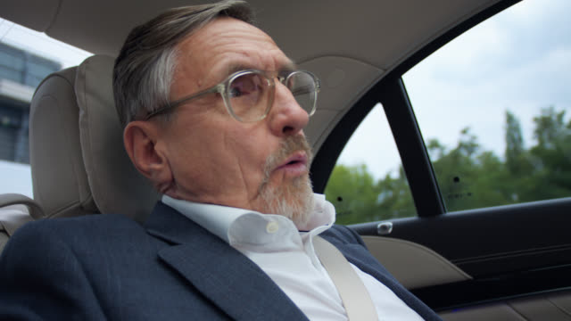 senior businessman in his 60s gets chauffeured in luxury limousine while sleeping and is waking up because of hard breaking - beifahrersitz oder rücksitz stock-videos und b-roll-filmmaterial