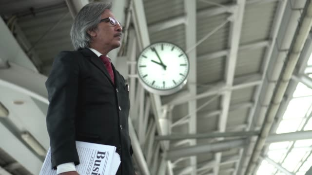 senior businessman is waiting train at platform in the morning - passenger train stock videos & royalty-free footage