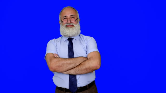 senior businessman looking into the camera with a smile and crossed arms on a blue background