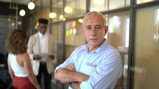 vidéos et rushes de portrait d'homme d'affaires aîné au bureau moderne de démarrage - quinquagénaire