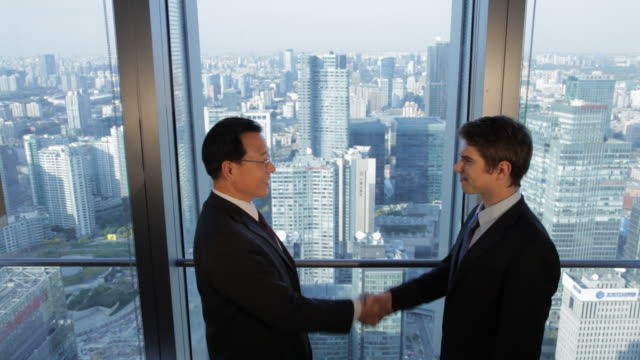 MS HA Senior businessman shaking hands with young businessman standing by office window, cityscape in background / Beijing, China