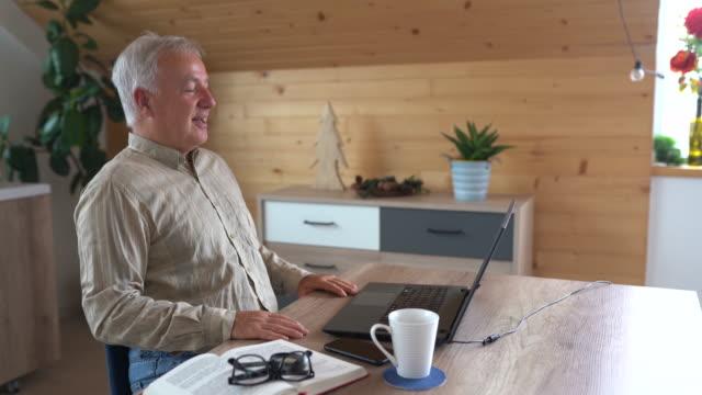 vidéos et rushes de homme d'affaires aîné s'asseyant à la table et ayant la conférence téléphonique à la maison - seniornaute