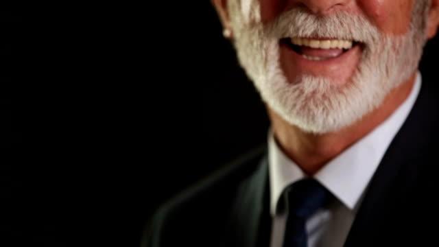 vídeos de stock e filmes b-roll de senior businessman smiling in studio on black background - sorriso aberto