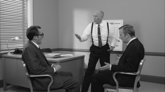 b/w ms senior businessman standing yelling at two sheepish  seated businessmen in office in front of graph showing loss/  men getting up and leaving office/ new york city - 1950 stock videos & royalty-free footage