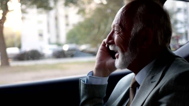 車の後部座席で携帯電話で話している上級ビジネスマン - 車内点の映像素材/bロール