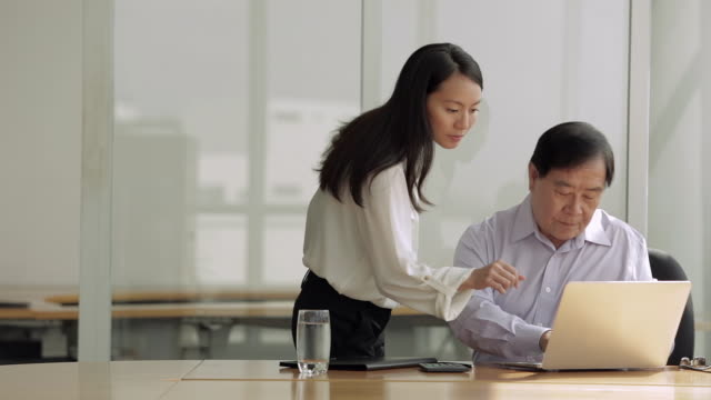 MS SELECTIVE FOCUS Senior businessman uses laptop while female colleague watches / Singapore