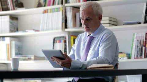 hd: senior businessman using digital tablet in office. - white hair stock videos & royalty-free footage