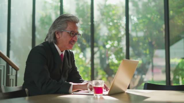 leitenden geschäftsmann mit seinem laptop und trinken kaffee in einem café. - mature adult stock-videos und b-roll-filmmaterial