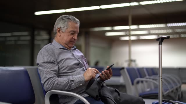 Senior Businessman Using Mobile Phone at Airport