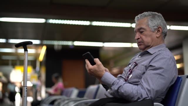 vídeos de stock, filmes e b-roll de homem de negócios sênior, usando telefone celular no aeroporto - área de embarque de aeroporto