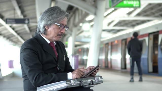senior affärsman använder surfplatta på perrongen - tunnelbaneplattform bildbanksvideor och videomaterial från bakom kulisserna