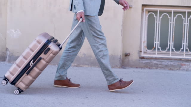Senior businessman walking with travel bag