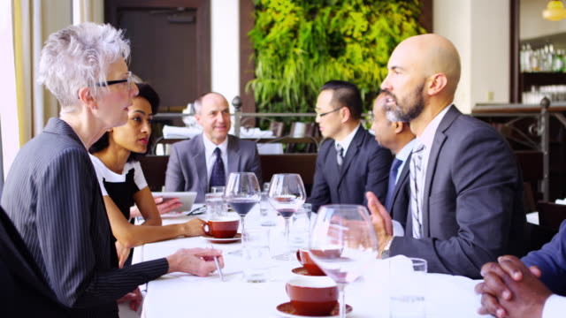 MS senior businesswoman listening to clients during business lunch meeting in restaurant.