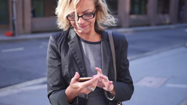 vidéos et rushes de femme d'affaires supérieur à l'aide d'un téléphone intelligent à londres - femmes seniors
