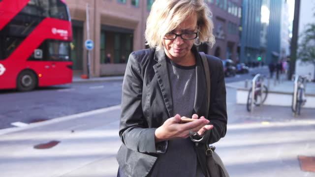 Femme d'affaires supérieur à l'aide d'un téléphone intelligent à Londres