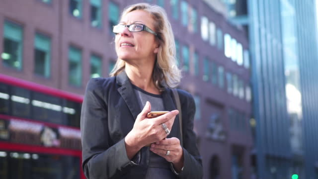 senior businesswoman using smart phone in london - eyeglasses stock videos & royalty-free footage