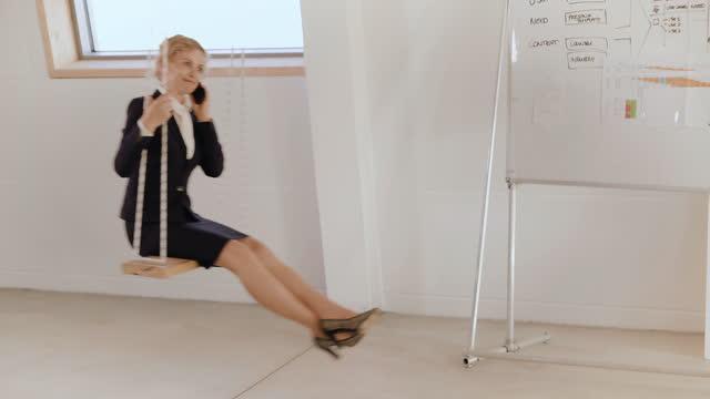 vídeos y material grabado en eventos de stock de senior businesswoman using smartphone on a swing - falda