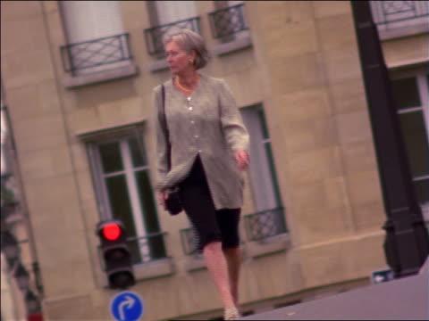 vídeos de stock e filmes b-roll de senior businesswoman walking on street towards camera / paris, france - trabalhadora de colarinho branco