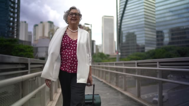 senior businesswoman walking with luggage at city bridge - luggage stock videos & royalty-free footage