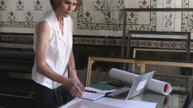 senior businesswoman with diary and laptop working at table in design studio - kurzes haar stock-videos und b-roll-filmmaterial
