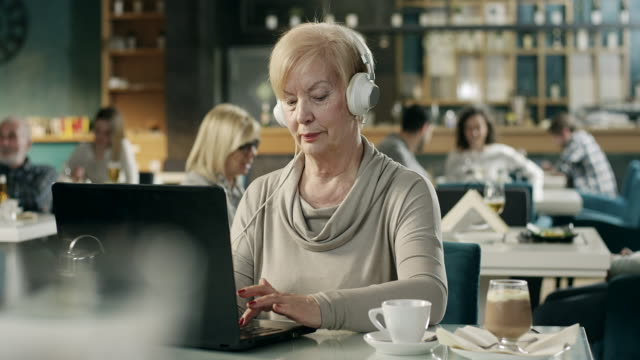 senior businesswoman working on laptop with hedphones on head in restaurant - one senior woman only stock videos & royalty-free footage
