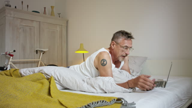 Senior but active and healthy man in his 60s with short greying hair and grey beard in his bedroom wearing undershirt, pyjama trousers and eyeglasses - falling on bed and using electronic devices.