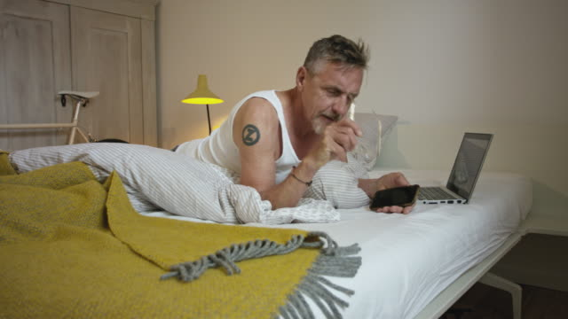 Senior but active and healthy man in his 60s with short greying hair and grey beard in bedroom wearing undershirt, pyjama trousers and eyeglasses using smart phone.