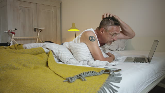 senior but active and healthy man in his 60s with short greying hair and grey beard in his bedroom wearing undershirt, pyjama trousers and eyeglasses using laptop. - schlafenszeit stock-videos und b-roll-filmmaterial