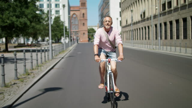 senior but active, sporty and healthy man in his 60s with short greying hair and grey beard enjoys urban lifestyle in summer, he wears leather sandals, short jeans and a red striped shirt while riding his trendy single speed city bike. - ヘッドフォン点の映像素材/bロール