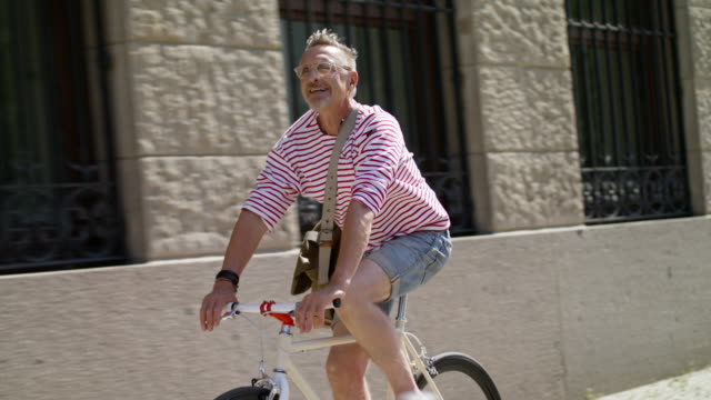 senior but active sporty and healthy man in his 60s with short greying hair and grey beard enjoys urban lifestyle in summer, he wears short jeans and a red striped shirt while riding his trendy single speed city bike. - ヘッドフォン点の映像素材/bロール