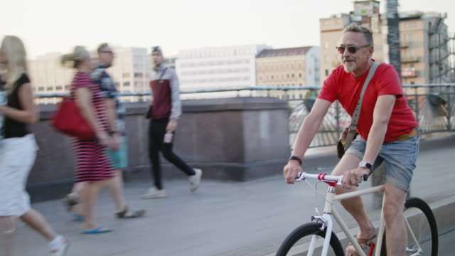 stockvideo's en b-roll-footage met senior but active, sporty and healthy man in his 60s with short greying hair and grey beard enjoys urban lifestyle in summer, he wears leather sandals, short jeans and a red t-shirt while riding his trendy single speed city bike. - alleen één seniore man