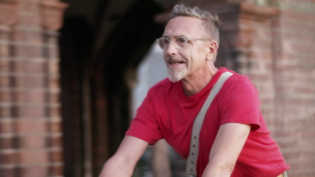 stockvideo's en b-roll-footage met senior but active, sporty and healthy man in his 60s with short greying hair and grey beard enjoys urban lifestyle in summer, he wears short jeans and a red t-shirt while riding his trendy single speed city bike. - alleen één seniore man
