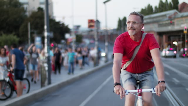 vídeos de stock e filmes b-roll de senior but active, sporty and healthy man in his 60s with short greying hair and grey beard enjoys urban lifestyle in summer, he wears short jeans and a red t-shirt while riding his trendy single speed city bike. - one senior man only