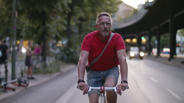 Senior but active, sporty and healthy man in his 60s with short greying hair and grey beard enjoys urban lifestyle in summer, he wears short jeans and a red T-shirt while riding his trendy single speed city bike.