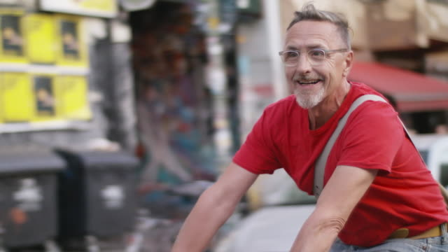 senior but active, sporty and healthy man in his 60s with short greying hair and grey beard enjoys urban lifestyle in summer, he wears short jeans and a red t-shirt while riding his trendy single speed city bike. - eyeglasses stock videos & royalty-free footage