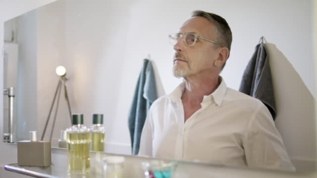 vídeos de stock e filmes b-roll de senior but handsome and still in good shape single man with short greying hair and grey beard in his early 60s gets ready for the next day in his bathroom. - espelho