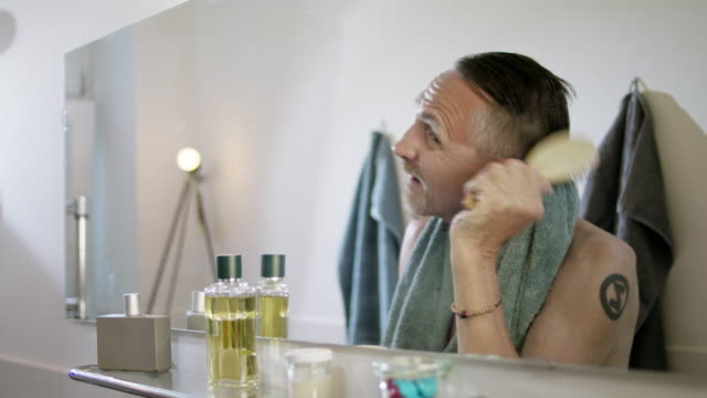 vídeos de stock e filmes b-roll de senior but handsome and still in good shape single man with short greying hair and grey beard in his early 60s gets ready for a new day in his bathroom. - toalha