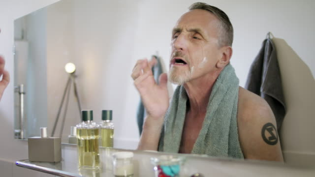 vídeos de stock e filmes b-roll de senior but handsome and still in good shape single man with short greying hair and grey beard in his early 60s gets ready for the next day in his bathroom. - máscara facial
