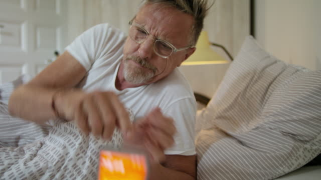 vídeos y material grabado en eventos de stock de senior but healthy and fit single man in his early 60s wakes up and getting up in the morning in his stylish bedroom, he wears a white t-shirt, pyjama trousers and glasses. - acostado