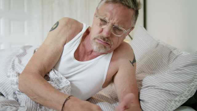senior but healthy and fit single man in his early 60s wakes up and gets up in the morning, he wears a white muscle shirt, pyjama trousers and glasses. - restlessness stock videos and b-roll footage
