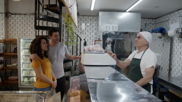 若いカップルが購入するための肉製品の重み付けシニア肉屋の男 - デリカッセン点の映像素材/bロール