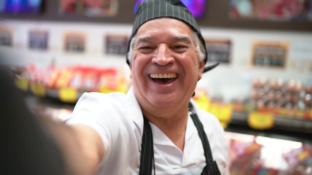 senior butcher taking a selfie in a butchers shop - butcher stock videos & royalty-free footage