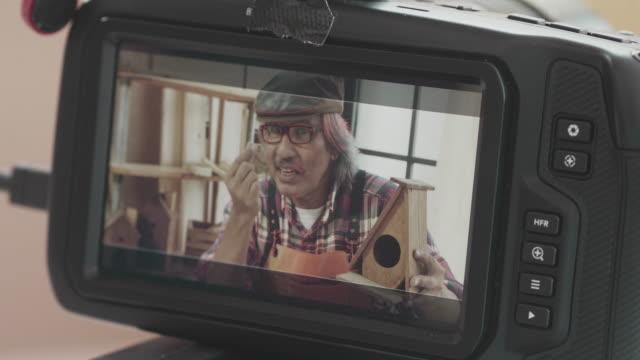 vidéos et rushes de blogueur charpentier aîné avec l'appareil-photo - artisanat