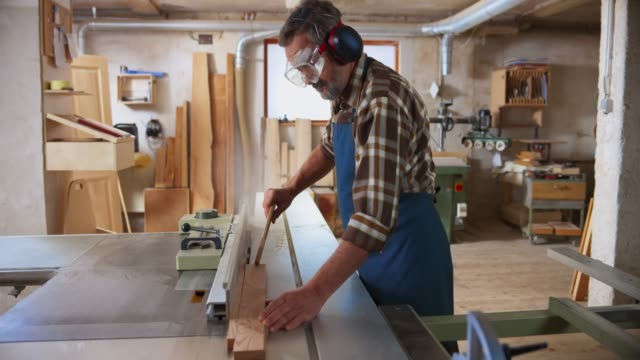 ds senior carpenter cutting a plank on his table saw in the workshop - manual worker stock videos & royalty-free footage
